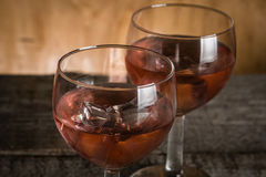 Glasses with rose wine on rustic wood background Royalty Free Stock Photography