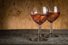 Glasses with rose wine on rustic wood background Stock Photography