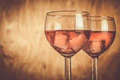 Glasses with rose wine on rustic wood background Stock Photos