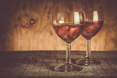 Glasses with rose wine on rustic wood background Royalty Free Stock Photos