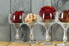 Glasses with roses symbolize wine. Shown on the background of stained plank stock photo