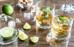 Glasses of rum. With lime and mint leaves on the wooden table royalty free stock photo