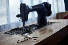 Glasses and sewing machine Stock Images