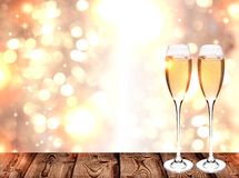Glasses of Champagne on Golden festive background. Festive bokeh background Golden color, two glasses with champagne standing on a wooden surface and offset Royalty Free Stock Photos