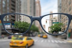 Glasses with sharp and blurred big city. 3d illustration of glasses with sharp and blurred big city stock photo