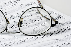 Glasses on sheet music. Close up photo of glasses on sheet music Royalty Free Stock Image