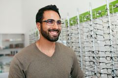 Glasses Shop. Man Trying On Eyeglasses In Optics Store royalty free stock photos