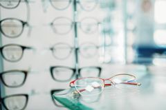 Glasses showcase in optic shop closeup, nobody. Eyes protection, eyeglasses on shelf in optical store, spectacles choice royalty free stock photos