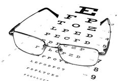 Glasses in a silver-rimmed on the Snellen eye chart Royalty Free Stock Images