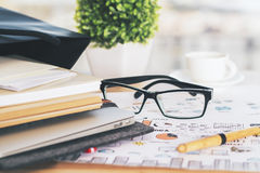 Glasses on sketch closeup. Closeup of desk with notepads, glasses and plant on business concept sketch stock photo
