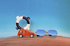 Small Orange car with lifebuoy on blue background. Glasses, small red car with lifebuoy on a blue background Royalty Free Stock Photo