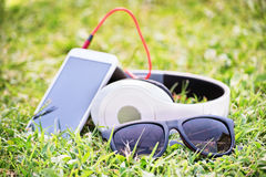 Glasses with smart phone and headphones on a meadow. Close-up shot of sunglasses with headphones and smart phone on e meadow Royalty Free Stock Images