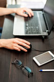 Glasses and smartphone on the table, laptop with human hands on a background Royalty Free Stock Photo