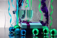 Glasses with sparkling champagne, gift, Christmas decorations on blue background Stock Photography
