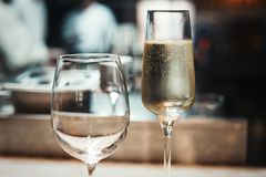 2 glasses with sparkling champaign with bubbles stand on the table in the restaurant. 2 glasses stand on the table in the restaurant. One glass is full with Stock Photo