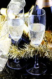 Glasses of sparkling wine. With bottles on a black background with decorations Royalty Free Stock Image