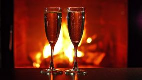 Glasses with sparkling wine. Close-up view of glasses with sparkling wine and fireplace on background stock footage