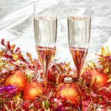 Glasses of sparkling wine with gold Xmas baubles Stock Photography