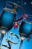 Glasses of sparkling wine. Two glasses of sparkling wine on a blue background with festive streamers stock images