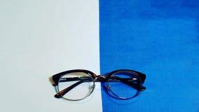 Glasses_specs del wafer sul contesto blu e bianco fotografia stock