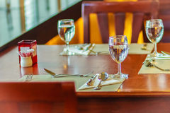 Glasses, spoon, frog, knife, napkin and plates on table setting Royalty Free Stock Photo