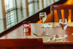Glasses, spoon, frog, knife, napkin and plates on table setting Royalty Free Stock Photography