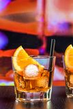Glasses of spritz aperitif aperol cocktail with orange slices and ice cubes on bar table, color pop atmosphere background Royalty Free Stock Image