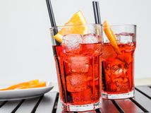 Glasses of spritz aperitif aperol cocktail with orange slices and ice cubes near plate of slices oranges Royalty Free Stock Image