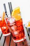 Glasses of spritz aperitif aperol cocktail with orange slices and ice cubes near plate of slices oranges Stock Image