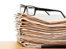 Glasses on a stack of newspapers Stock Photo