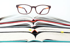 Glasses on stack of open books Stock Photos
