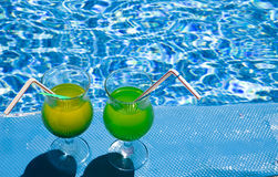Glasses stand with cocktail. On edge of pool royalty free stock image