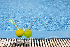 Glasses stand of pool. Glasses stand with cocktail on edge of pool royalty free stock photos