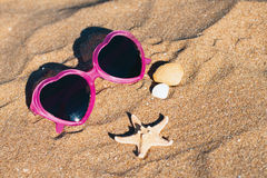 Glasses and shells in the sand Royalty Free Stock Photos