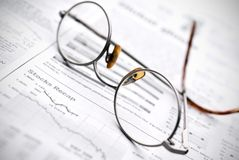 Glasses on a stock report. Glasses on a newspaper stock report Stock Photos