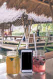 Glasses of strawberry and mango juices with soda on a wooden table and smartphone with black screen. Tropical cafe stock photos