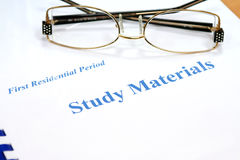 Glasses on the study materials Royalty Free Stock Photo