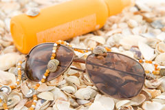 Glasses, sunscreen cream and beads on shells Stock Photography