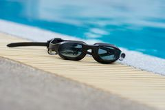 Glasses for swimming black on pool edge Royalty Free Stock Photos