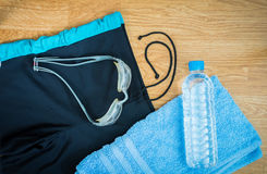Glasses and Swimming trunks , water Bottles , towel. On wooden background Stock Photo