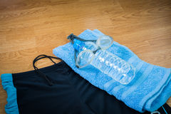 Glasses and Swimming trunks , water Bottles , towel. On wooden background Stock Image