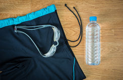 Glasses and Swimming trunks and water Bottles. On wooden background Stock Photo