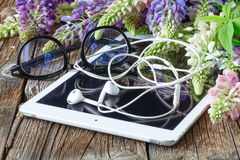 Glasses on tablet  and flowers Royalty Free Stock Image