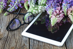 Glasses on tablet  and flowers Stock Photos