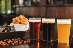 Glasses of tasty beer and snacks on wooden table. In bar stock photos