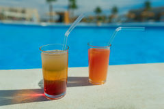 Glasses with tasty cocktail in front of a swimming pool with clear water. Close-up photo. Palm trees on the background. Vacation a Stock Image