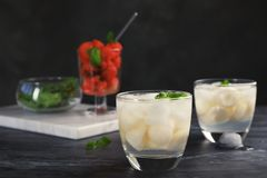 Glasses with tasty melon ball drinks. On dark table stock images