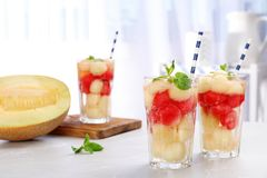 Glasses with tasty melon and watermelon ball drink. On light table stock photos