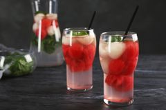 Glasses with tasty melon and watermelon ball drinks. On dark table royalty free stock photo