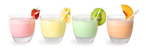 Glasses of tasty milk shakes on white backgroun. D royalty free stock image